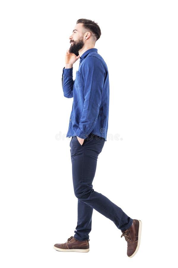 Homme réussi sûr heureux d'affaires marchant et parlant au téléphone portable avec des mains dans des poches recherchant image libre de droits