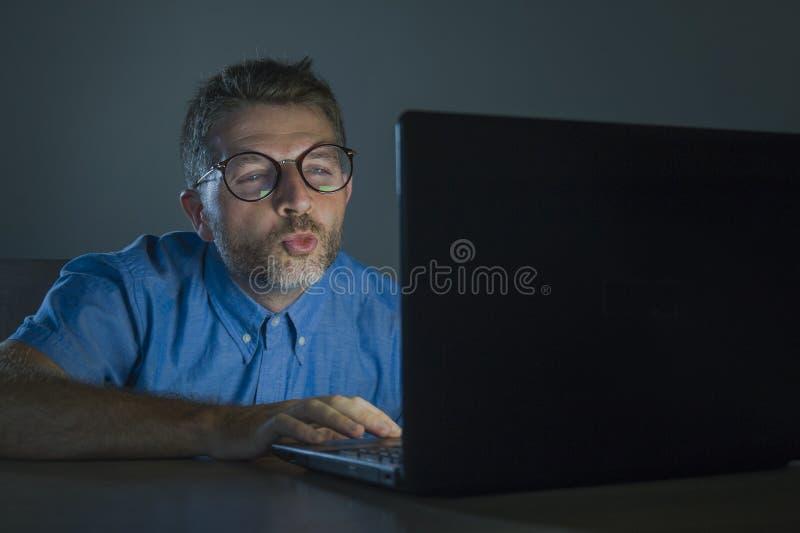 Homme réveillé lascif d'intoxiqué de porno en verres de ballot observant le film de sexe en ligne de fin de nuit à l'ordinateur p photo libre de droits