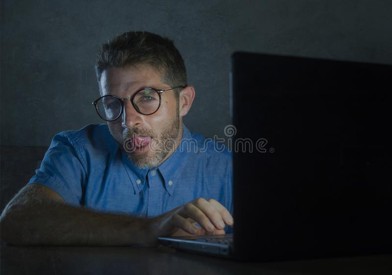 Homme réveillé lascif d'intoxiqué de porno en verres de ballot observant le film de sexe en ligne de fin de nuit à l'ordinateur p photo stock