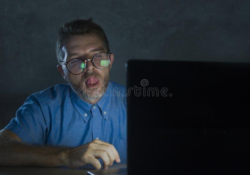 Homme réveillé lascif d'intoxiqué de porno en verres de ballot observant le film de sexe en ligne de fin de nuit à l'ordinateur p image stock