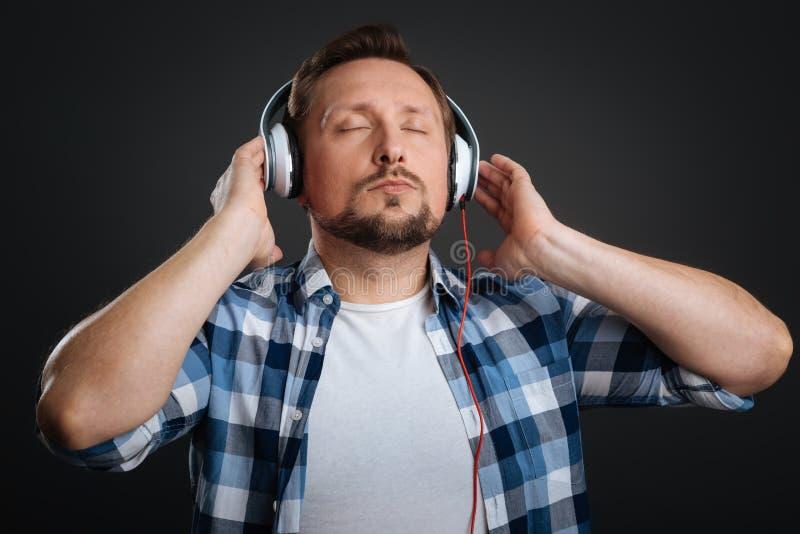 Homme rêveur bel attrapé dans la musique photos stock