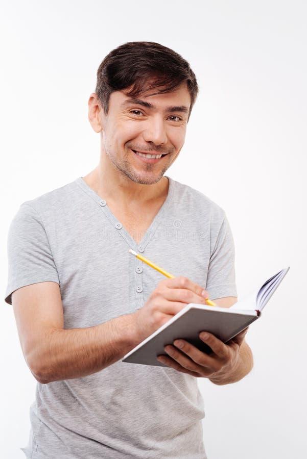 Homme raidi agréable faisant des notes dans le carnet images stock