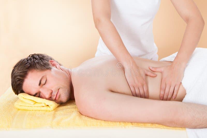 Homme recevant de retour le massage dans la station thermale photo stock