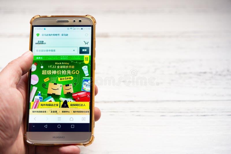 Homme recherchant des produits de ventes de Black Friday sur Amazone Chine par le mobile photographie stock