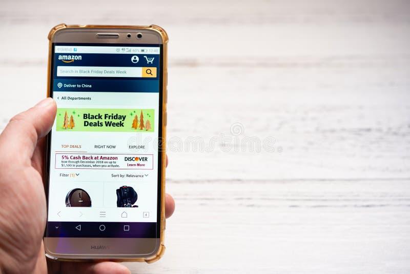 Homme recherchant des produits de ventes de Black Friday sur Amazone par le mobile photos libres de droits