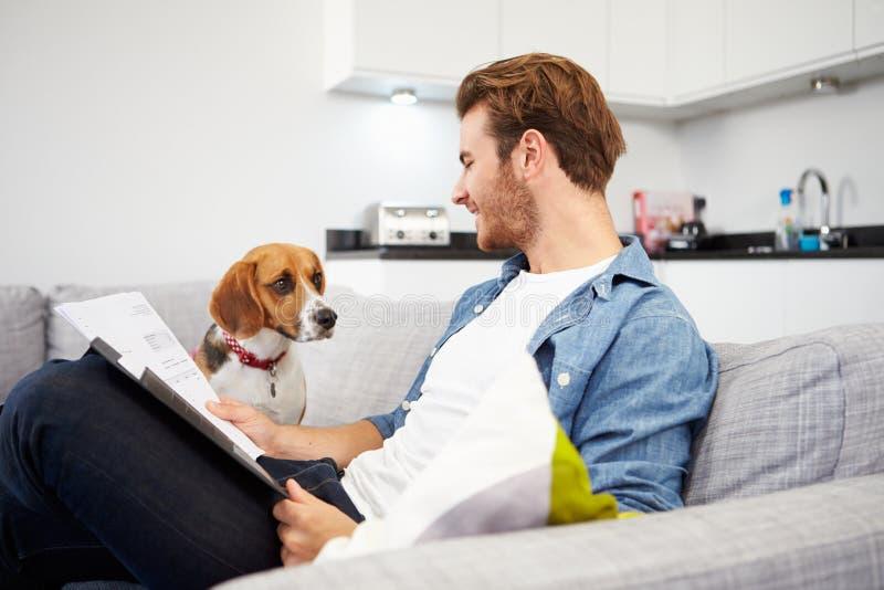 Homme regardant des écritures et jouant avec le chien  image stock