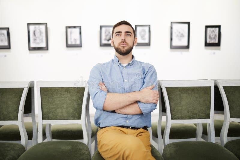 Homme regardant des peintures en Art Gallery photographie stock