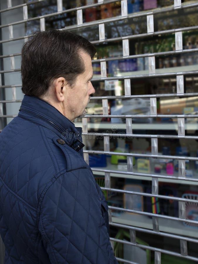 Homme regardant la fenêtre de magasin dans un magasin fermé images libres de droits