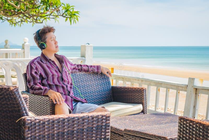 Homme regardant la mer et écoutant la musique à la terrasse de bord de mer photographie stock