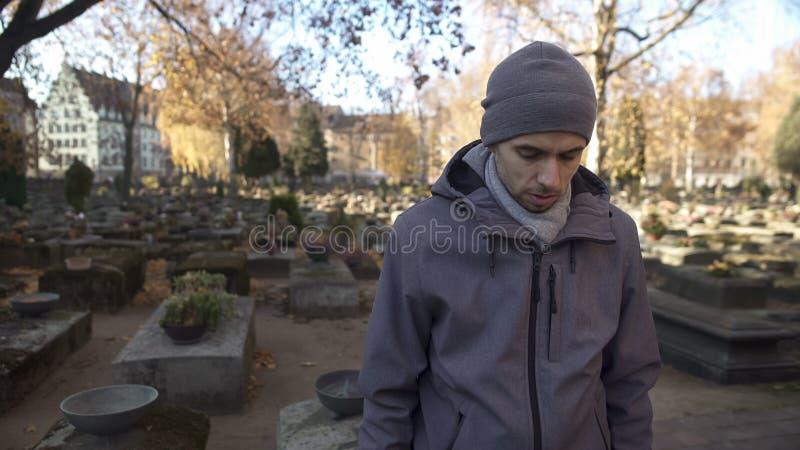 Homme regardant la pierre tombale le cimetière, priant et partageant des nouvelles avec des défunts images stock