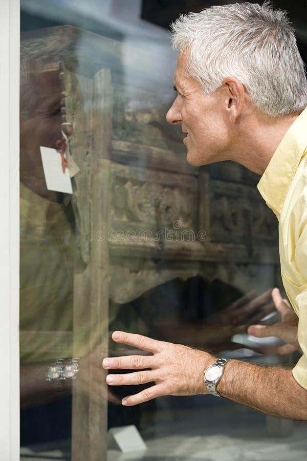 Homme regardant la raboteuse dans la fenêtre de boutique photos libres de droits
