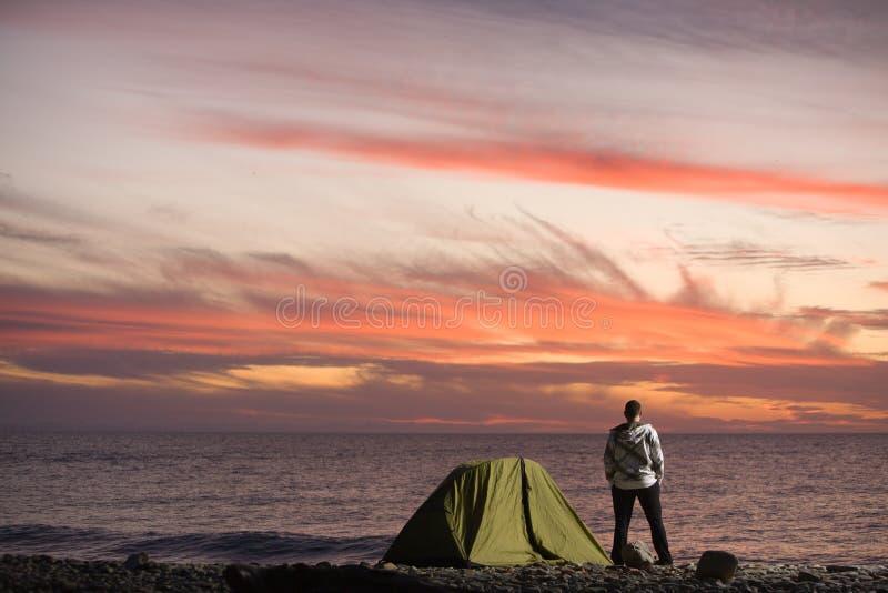 Homme regardant le coucher du soleil photo stock