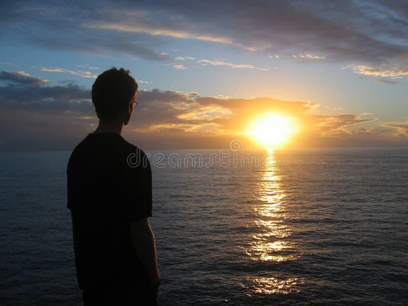 Homme regardant le coucher du soleil photographie stock