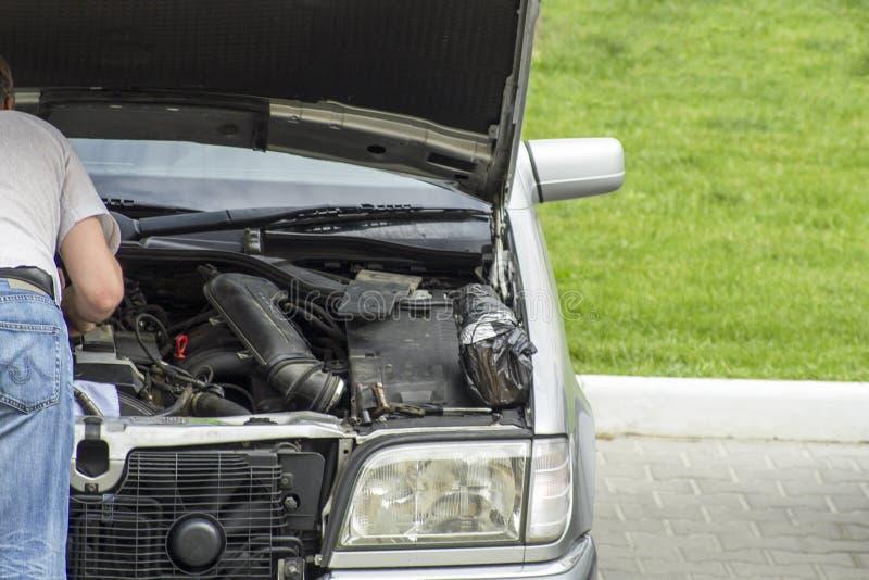 homme regardant le moteur de voiture décomposé par le côté de la route photo stock