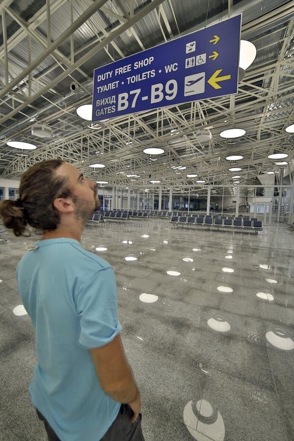 Homme regardant le panneau d'affichage dans l'aéroport photos libres de droits