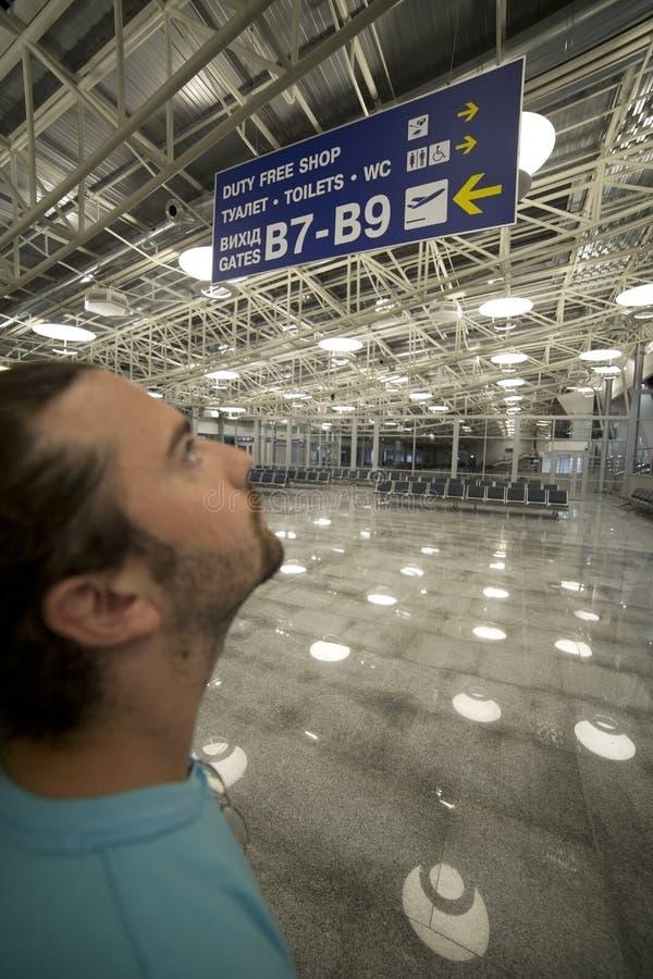 Homme regardant le panneau d'affichage dans l'aéroport photographie stock