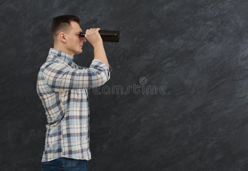 Homme regardant par des lunettes de bière photographie stock