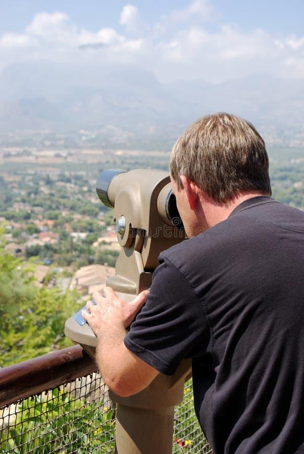 Homme regardant par le télescope de vue. Barre verticale photo stock
