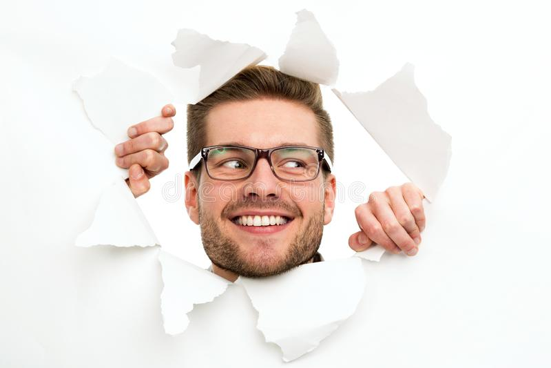 Homme regardant par le trou en papier images libres de droits