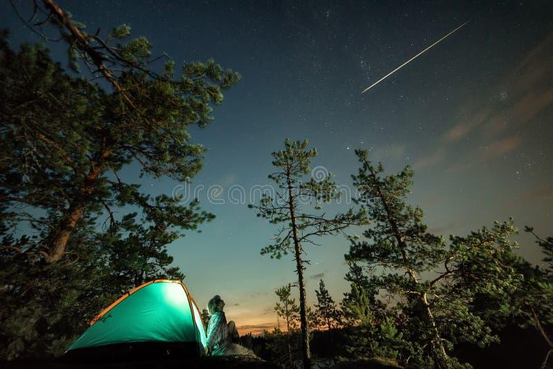 Homme regardant sur le ciel étoilé proche avec l'étoile filante photo libre de droits