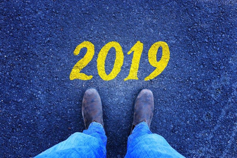 Homme regardant vers le bas ses pieds sur la route goudronnée avec le nombre 2019 peint là-dessus images stock