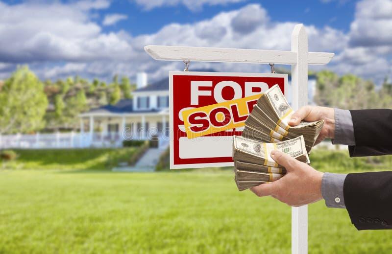 Homme remettant l'argent en Front Sold House et signe images stock