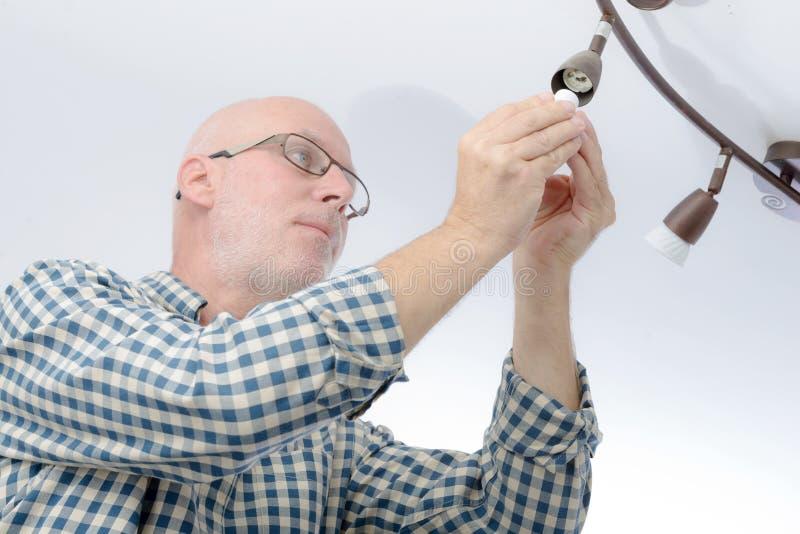 Homme remplaçant l'ampoule à la maison photographie stock libre de droits