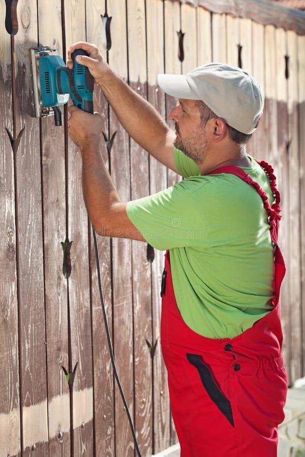 Homme remplaçant une barrière en bois photographie stock