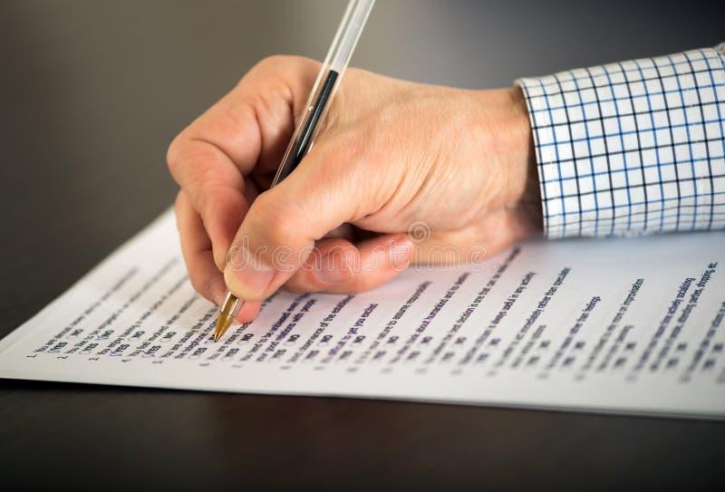 Homme remplissant un questionnaire photographie stock libre de droits