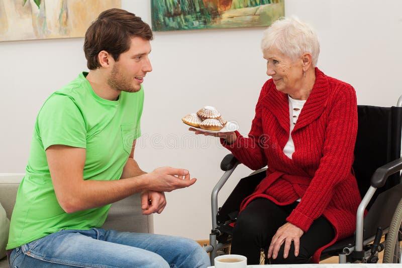 Homme rendant visite à sa tante handicapée photos stock