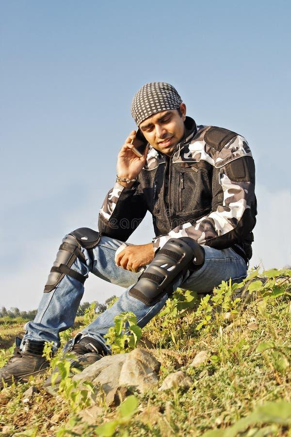 Homme reposé au bord de la route utilisant le téléphone portable photographie stock