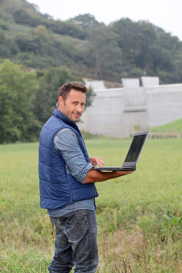 Homme restant dans le domaine avec l'ordinateur portatif photo stock