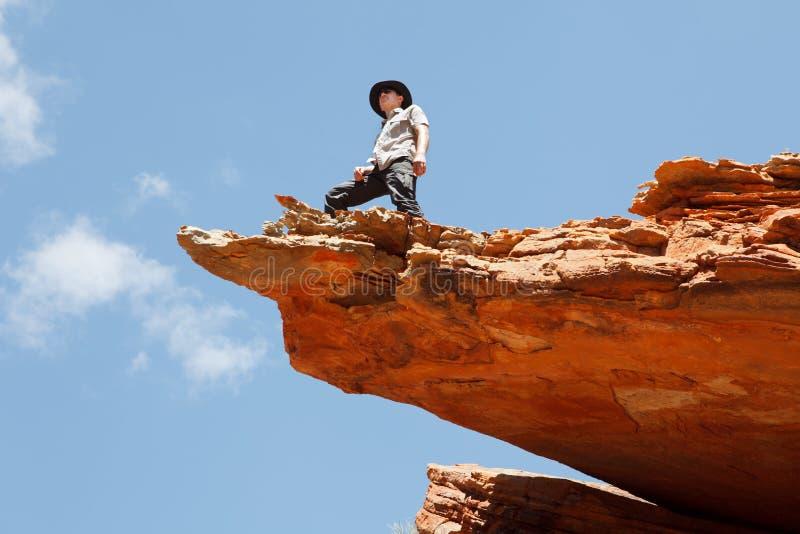 Homme restant sur le bord de roche photographie stock