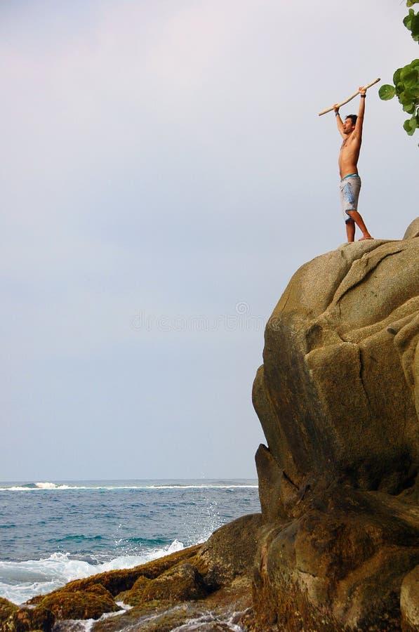 Homme restant victorieusement sur une falaise photos stock
