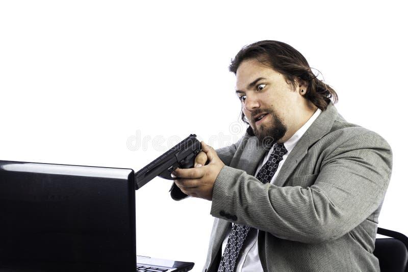 Homme retenant le canon sur l'ordinateur portable photo libre de droits