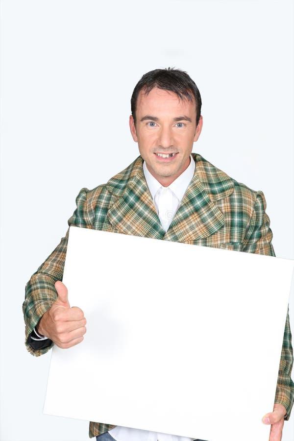 Homme retenant un panneau blanc photographie stock