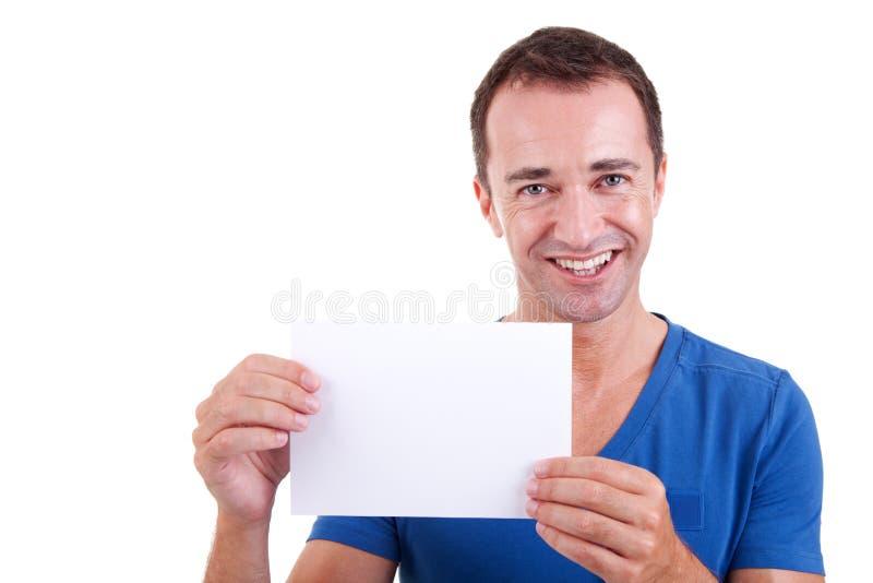 Homme retenant une carte blanche, souriant image libre de droits