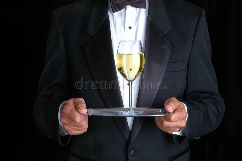 Homme retenant une glace de vin sur un plateau photographie stock libre de droits