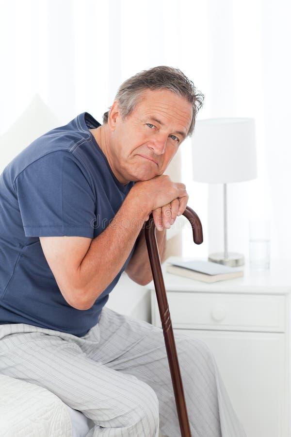 Homme retiré avec son bâton de marche images stock