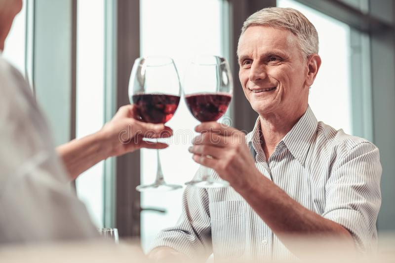 Homme retiré bel buvant du vin rouge dans un restaurant image stock