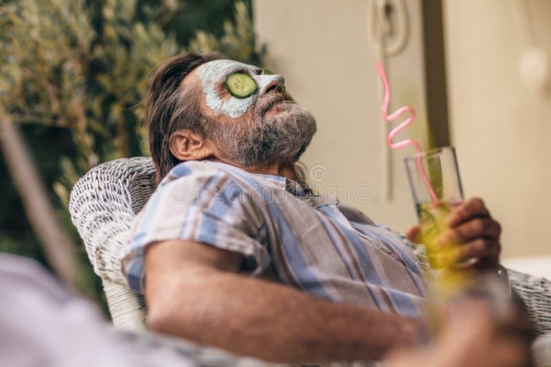 Homme retiré détendant avec le masque d'argile sur le visage photographie stock