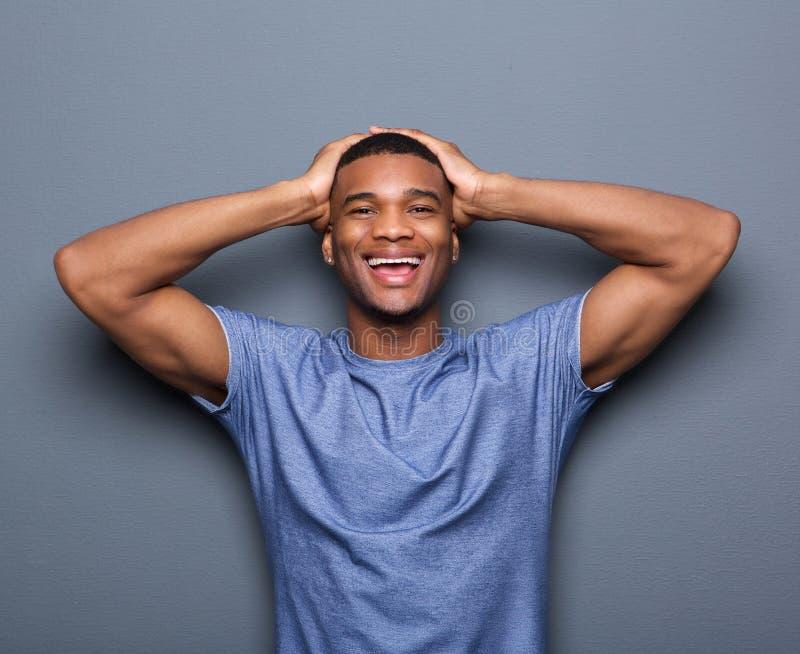Homme riant avec des mains sur la tête photographie stock libre de droits