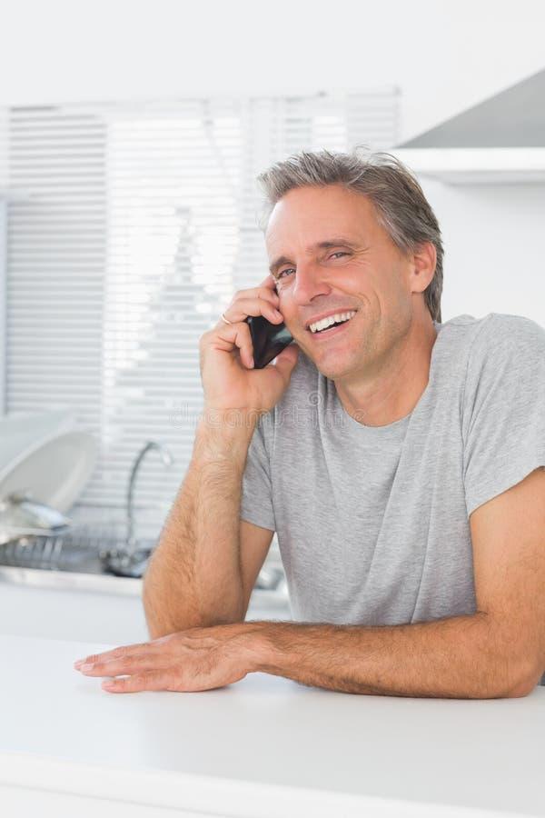 Homme riant faisant l'appel téléphonique dans la cuisine image stock