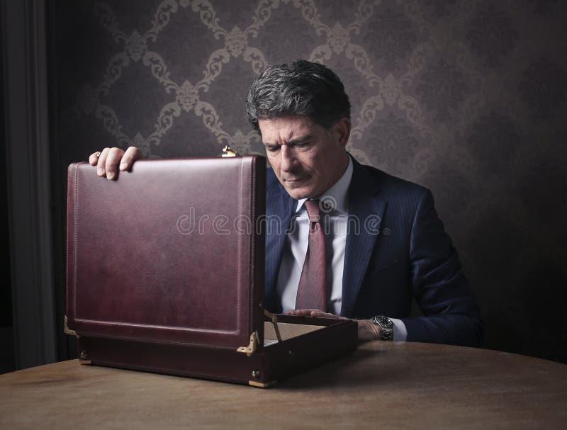 Homme riche élégant ouvrant sa serviette images stock