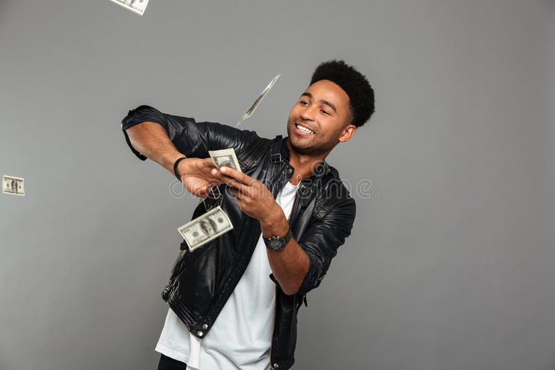 Homme riche afro-américain drôle dispersant des billets de banque des dollars images stock