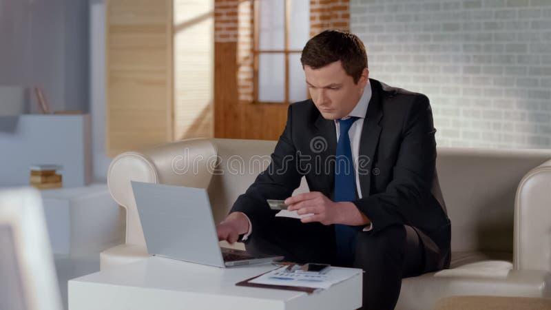 Homme riche dans le costume payant avec la carte de banque utilisant l'ordinateur portable, transaction en ligne d'argent image libre de droits