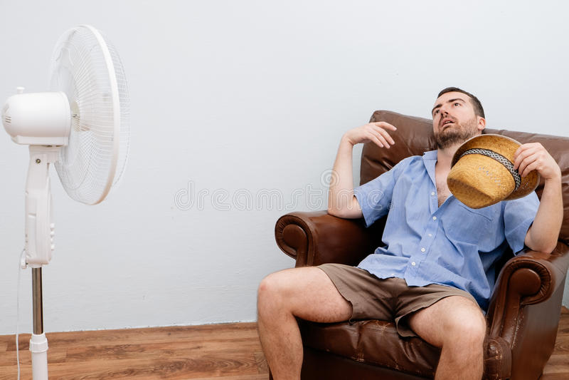 Homme rincé se sentant chaud devant une fan images libres de droits
