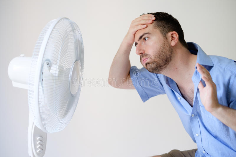 Homme rincé se sentant chaud devant une fan photos libres de droits