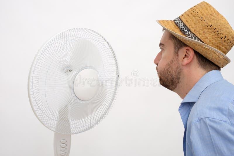 Homme rincé se sentant chaud devant une fan image libre de droits