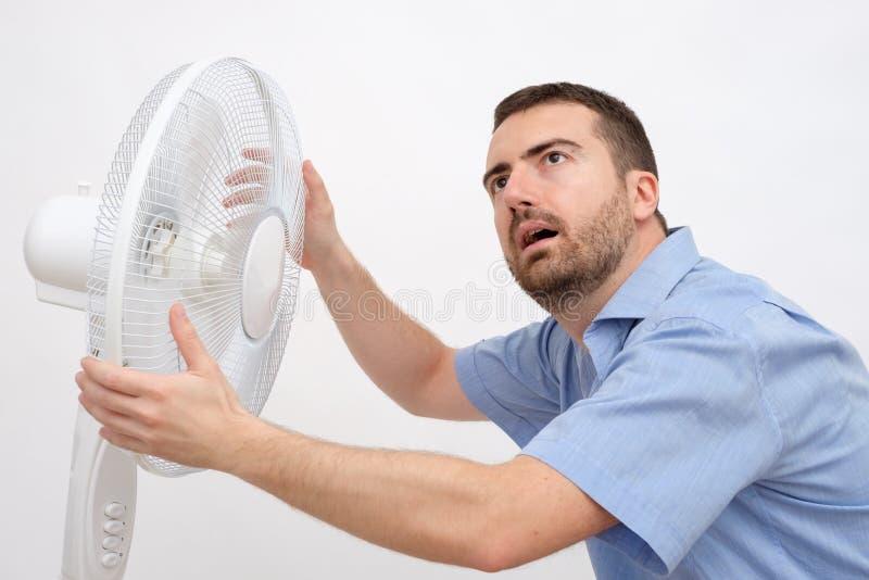 Homme rincé se sentant chaud devant une fan photographie stock